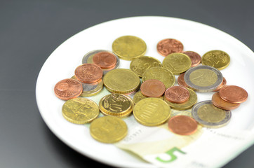 Münzen auf Teller