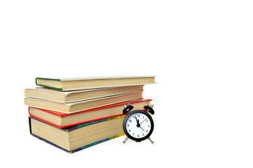 Alarm clock and  books isolated on white background
