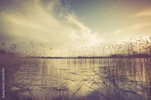 Vintage photo of beautiful sunset over calm lake - 83415459