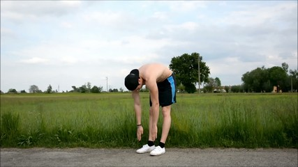 Shirtless young man outdoor doing stretching exercises