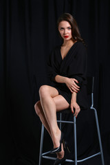 Beautiful woman sitting a chair, isolated on lack background