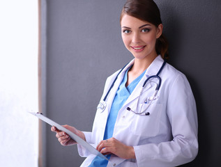 Young doctor or medic with clipboard and stethoscope isolated on