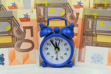 Miniature clock with banknotes in the background