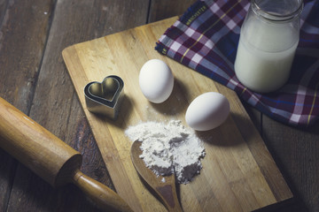 Flour and eggs on a wooden table