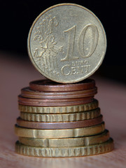 Ten euro cent coin balancing on a top of coins pile.