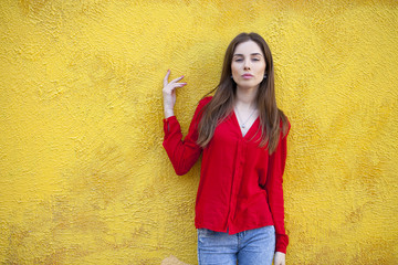 Sexy young woman, against the background of the yellow wall