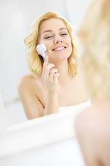 Woman using face cleansing brush