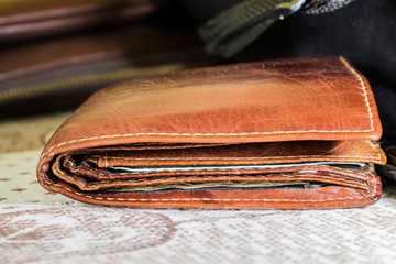 close-up brown leather wallet of traveler on table