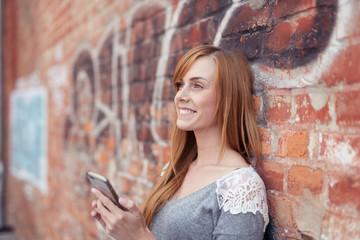 lächelnde frau mit ihrem mobiltelefon