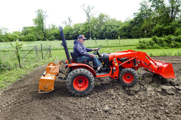 Older Farmer Tilling His Garden With His Compact 4x4 Tractor