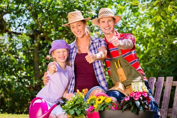 Paar mit Schlauch gießt im Garten
