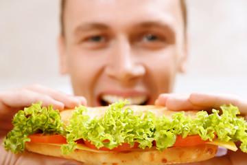 Close up of man taking bite sandwich