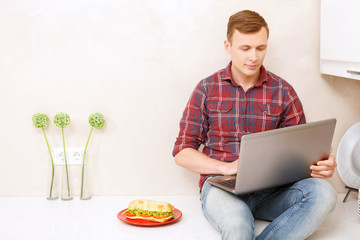 Man sitting with computer in kitchen