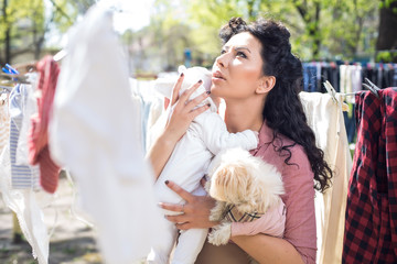 Mother with baby doing laundry outdoors