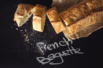 French baguette on black chalkboard from above.