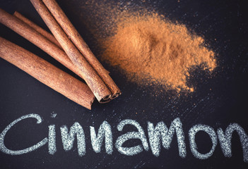 Cinnamon sticks on black chalkboard from above.