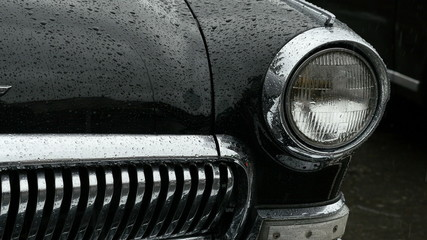 Headlight and front side of old car in the rain.