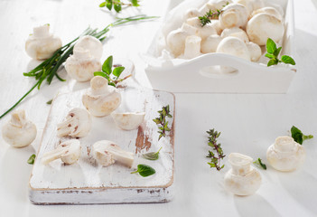Fresh whole white button mushrooms  on  a wooden cutting board.
