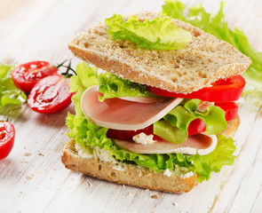 Sandwich with turkey and fresh vegetables on  a wooden table