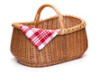 Wicker picnic basket with red checked napkin.