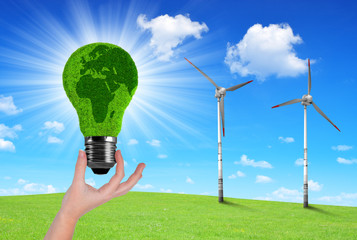 Eco Light bulb in hand in the background wind turbines