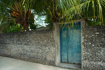 Coral wall and door in front of a garden in the Maldives
