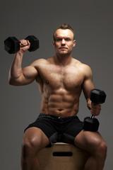 Shirtless muscular man with dumbells