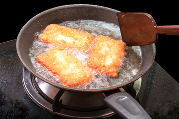 breaded chicken pieces being deep fried in a cast iron pan