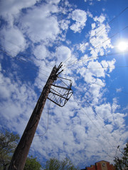 Wooden post with electric wires against the blue sky