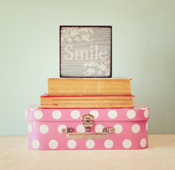 photo of pink suitcase with polkadots and stack of books