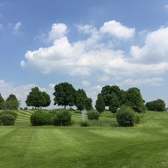 Golf field with cloudy blue sky