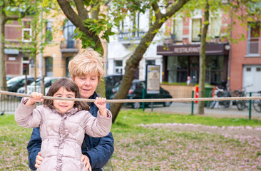 Young girl with grandmother happy at the playground