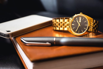 Men's accessory, golden watch, pen and mobile phone on the