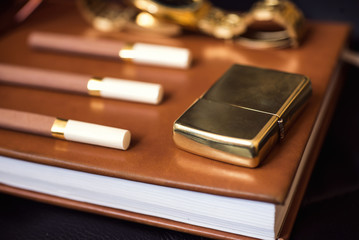 Men's accessory, golden lighter, watch and cigarettes on the