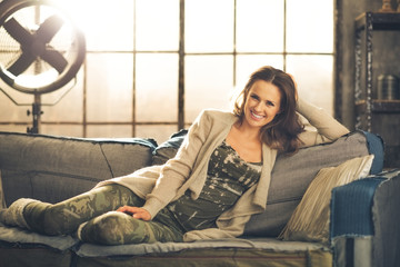 Woman front-facing sitting on sofa in loft relaxing smiling