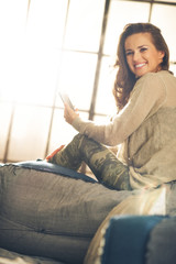 Woman in loft smiling and looking over shoulder holding phone
