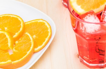 plate of slices oranges near glass of spritz aperitif cocktail