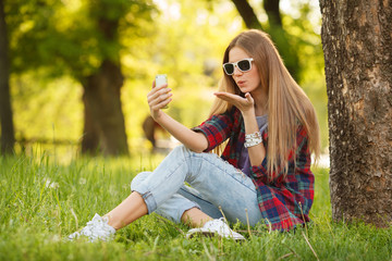 beautiful woman takes selfie on cell phone in summer city park