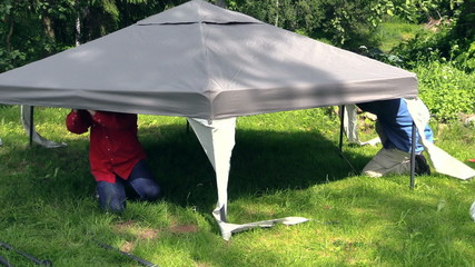 Zoom in father and son fix tent cloth roof on garden arbor