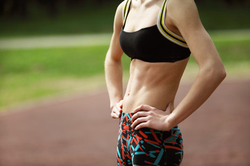Image of athletic young woman with tight defined abs in stomach
