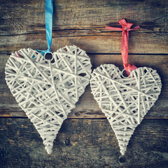 Two wicker hearts hanging on old wooden wall.