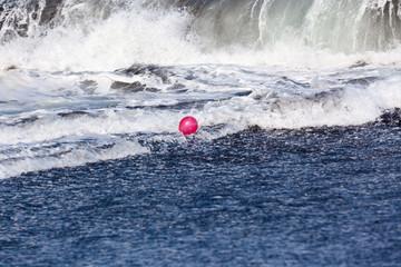 ballon rouge dans l'écume des vagues