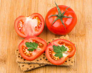 Wheat crisp bread and tomato on bamboo board