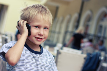 Boy speaks on a mobile phone in supermarket, tinted photo.