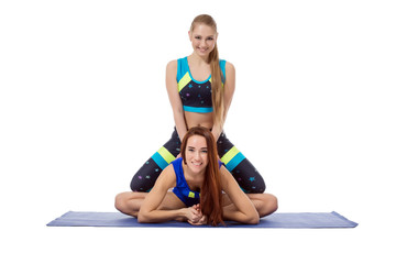 Smiling girl helps her friend to stretch