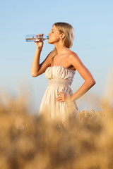 Woman drinking water in wheat field