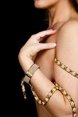 Naked woman in jewelry - a gold bracelet and a gold chain