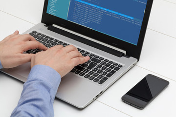 Developer working on source codes on laptop at office