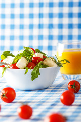 Salad mix, arugula, cherry tomato and cheese with orange juice