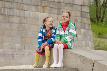 Two girls sit on a granite ramp